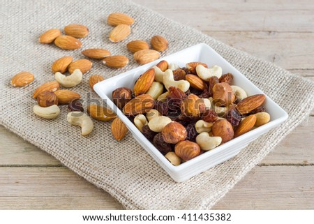 Nuts in a white bowl on a sack, wooden background - stock photo