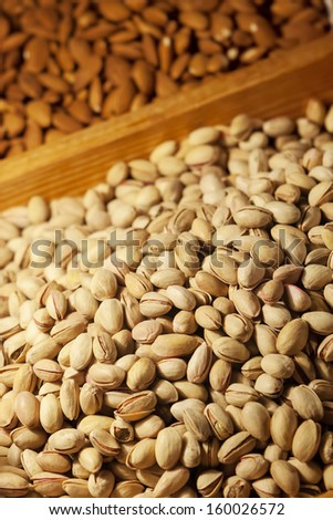 Nuts in row/Pistachio and almond on market. Plenty of organic seed. - stock photo