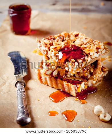Nuts,maple syrup and honey caramel tart on a wooden background - stock photo