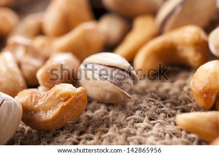 Nuts mix, selective focus on the pistachio in middle - stock photo