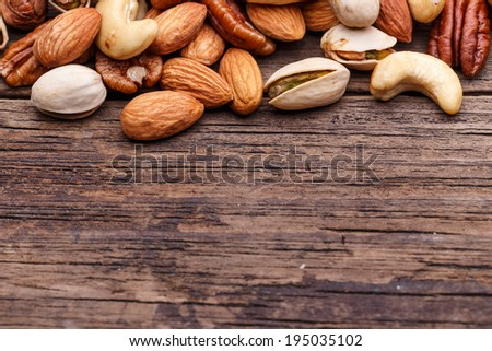 Nuts mix, with almond, cashews, pistachios, pecans, hazelnuts on wood plank background - stock photo