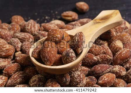 nuts, salted almonds, in wooden spoon - stock photo