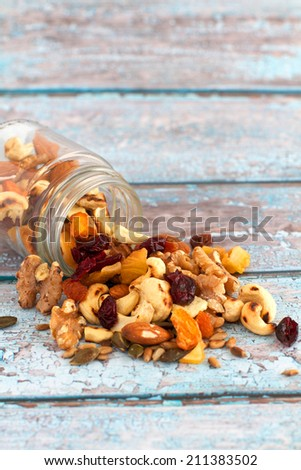 Nuts Seeds and Dried Fruit on a painted wooden background