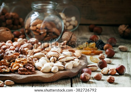 Nuts set of pistachios, walnuts, almonds and hazelnuts on a wooden background, selective focus - stock photo
