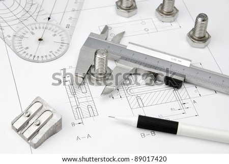 nuts wrench and caliper on technical drawing - stock photo