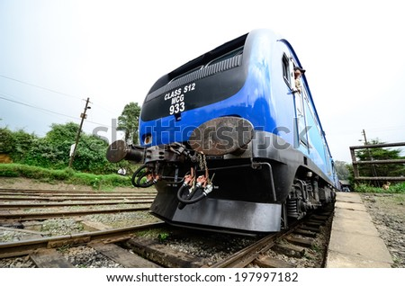 NUWARA ELIYA, SRI LANKA - MAR 23: Train arrive to station with people on March 23, 2013 in Nuwara Eliya, Sri Lanka. Trains are becoming more popular transport due to railway improvement by government - stock photo