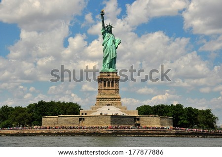 NY - AUG 3, 2013:  The Statue of Liberty standing atop a stone octagonal base with crowds of tourists  * - stock photo