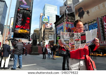 NY - OCT 08:Man reads a brochure of Broadways shows in Time Square on October 08 2010.It's one of the world's busiest pedestrian intersections and a major center of the world's entertainment industry. - stock photo