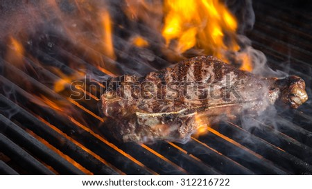 NY Strip Steak on Grill with Flames - stock photo