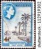 NYASALAND - CIRCA 1953: A stamp printed in Nyasaland shows fishing village, lake Nyasa with Queen Elizabeth II, circa 1953. - stock photo