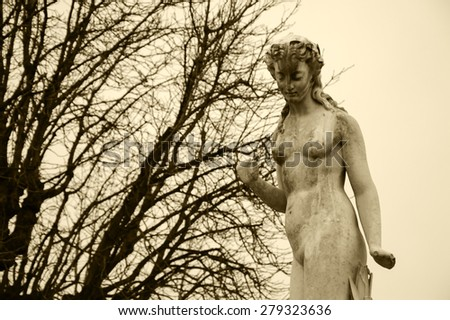 Nymphe marble statue in Tuileries gardens in cloudy winter day. Aged photo. Sepia. - stock photo