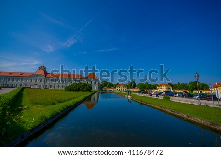 Nymphenburg, Germany - July 30, 2015: Idyllic part of palace gardens with quiet blue river channel and large buildings in background.