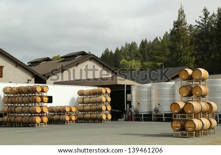 Oak barrels and stainless steel fermentation tanks at the vineyard - stock photo