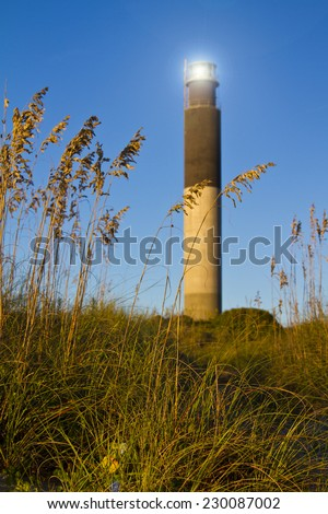 Oak Island Southport North Carolina Lighthouse through the Casswell Beach seagrass at sunset - stock photo