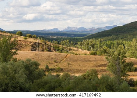 Oak Woodland landscape with mountains in the background - Beautiful rolling summer landscape with forests of oaks, pines, poplars and willows. Wide visibility that reveals the background mountains  - stock photo