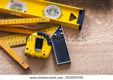 Oaken board with wooden meter measuring line construction level and square ruler maintenance concept  - stock photo