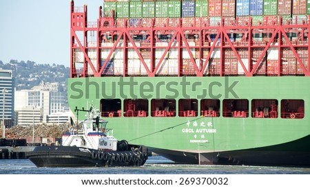 OAKLAND, CA - APRIL 12, 2015: AmNav Tugboat SANDRA HUGH at the stern of CSCL AUTUMN. American Navigation was a pioneer in developing tugboats with high horsepower engines in relatively small hulls. - stock photo