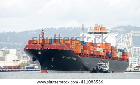 Oakland, CA - April 24, 2016: Cargo Ship ROTTERDAM EXPRESS with tugboat Z-FOUR off the port side assisting the vessel to maneuver into the Port of Oakland. - stock photo