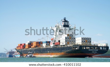 Oakland, CA - April 13, 2016: Cargo Ship SEASPAN NINGBO with Tugboat Z-THREE on the Port side , assisting the vessel to maneuver into the Port of Oakland.