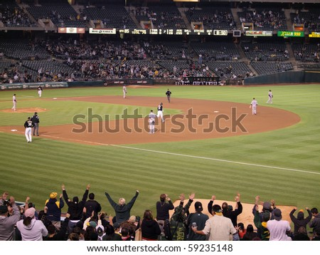 OAKLAND, CA - AUGUST 16: Blue Jays vs. Athletics: Athletics fans celebrate home run as Conor Jackson rounds the base after hitting homerun on August 16, 2010 at Coliseum in Oakland California.