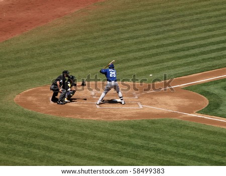 OAKLAND, CA - AUGUST 4: Royals vs. Athletics: Kila Ka'aihue batting looks at a incoming fastball with  Kurt Suzuki catching, umpire behind him.  August 4 2010 at Coliseum in Oakland California. - stock photo