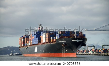 OAKLAND, CA - DECEMBER 29, 2014:  Cargo Ship APL HOLLAND entering the Inner Harbor at the Port of Oakland with Tugboat DELTA CATHRYN following at the Stern. - stock photo