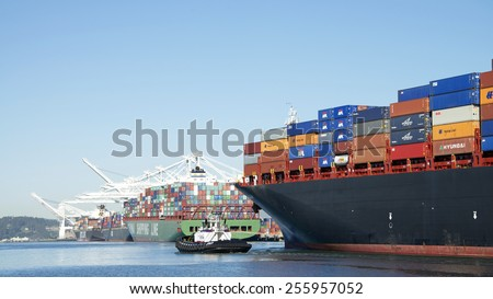 OAKLAND, CA - FEBRUARY 24, 2015: AmNav Tugboat PATRICIA ANN leading APL Cargo Ship SALALAH, heavily loaded with shipping containers, out of the Port of Oakland. - stock photo