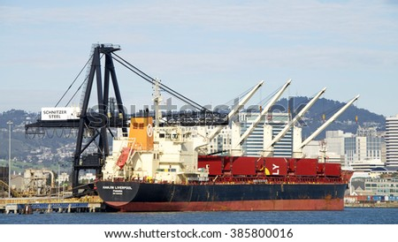 Oakland, CA - February 27, 2016: Bulk Carrier HANJIN LIVER:POOL docked at Schnitzer Steel at the Port of Oakland. Trucks load scrap metal to be recycled over seas.