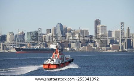 OAKLAND, CA - FEBRUARY 23, 2015: Pilot Vessel GOLDEN GATE heading towards the Bay Bridge in the San Francisco Harbor. San Francisco City seen in the background. - stock photo