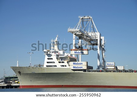 OAKLAND, CA - FEBRUARY 24, 2015: Presumably an new crane operator loading the MANOA at the Port of Oakland as containers hit the cell guide loudly, then adjusted to slide into place for each container