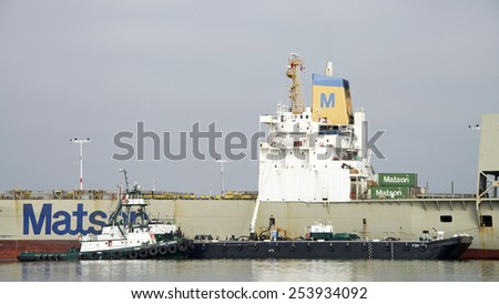 OAKLAND, CA - FEBRUARY 18, 2015: Tugboat POINT VINCENTE pushed a Barge up next to  Matson Cargo Ship MATSONIA to provide services. The Cargo Ship has been inactive at the Port of Oakland for months.