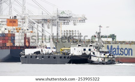 OAKLAND, CA - FEBRUARY 17, 2015: Tugboat ROYAL MELBOURE pushing BERNIE BRIER, a double hulled barge ship, past the Port of Oakland. A tugboat maneuvers vessels by pushing or towing them. - stock photo