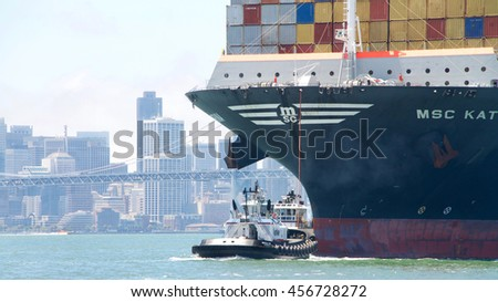 Oakland, CA - July 18, 2016: PATRICIAN ANN off the bow of MSC KATRINA, assisting the vessel to maneuver into the Port of Oakland. Tugboats are vital for safe, efficient entry and exit for large ships.