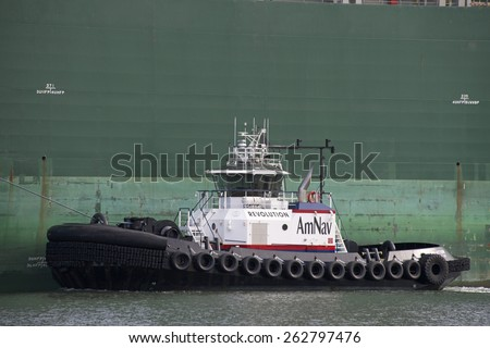OAKLAND, CA - MARCH 22, 2015: AmNav tugboat REVOLUTION performing tugboat assistance. American Navigation was a pioneer in developing tugboats with high horsepower engines in relatively small hulls. - stock photo