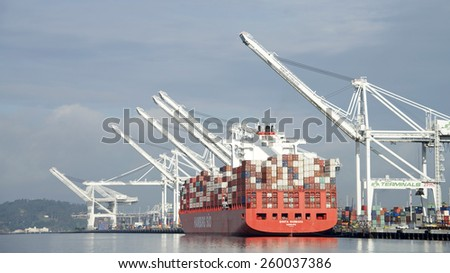 OAKLAND, CA - MARCH 11, 2015: Hamburg SUD Cargo Ship SANTA BARBARA docked at the Port of Oakland. Loading completed, the ship waits for tugboat assistance to depart the port.