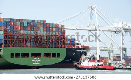 OAKLAND, CA - MAY 03, 2015: China Shipping Lines Cargo Ship CSCL SPRING entering the Port of Oakland with Tugboat VALOR at the stern.