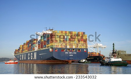 OAKLAND, CA - NOVEMBER 25, 2014: Tugboat AMERICA is at the stern with MARSHAL FOSS on the starboard quarter and P/V GOLDEN GATE PILOT on the port bow escorting CMA CGM LYRA out of the Port of Oakland. - stock photo