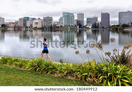 OAKLAND, CALIFORNIA - JAN. 11, 2014: A jogger runs on the 3.4 mile path around Lake Merritt in downtown Oakland.The shoreline was recently renovated, adding new parks and an amphitheater. - stock photo