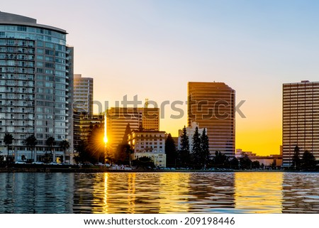 Oakland Lake Merritt skyline backlit at sunset with sun flare between buildings and reflections on the lake. Viewed from the water. Copy space. - stock photo