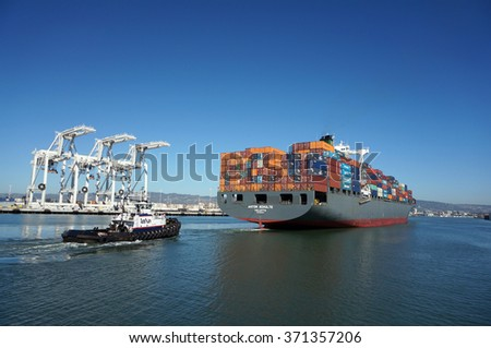 OAKLAND - OCTOBER 12: Fully loaded Shipping Cargo Boat pushed through harbor under giants unloading cranes in Oakland Harbor.  Oakland California on October 12, 2015. - stock photo
