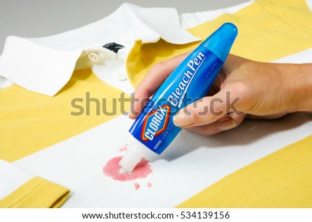 OAKLAND, USA - JUL 07, 2005: Clorox Bleach Pen Held by a woman's hand  being used on a stained shirt