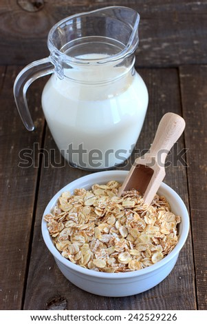 Oat, barley and wheat flakes in a ceramic bowl and a jug with milk - stock photo