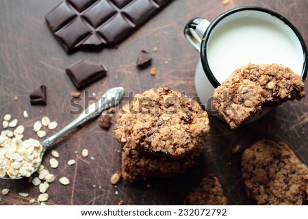 Oat cookies with dark chocolate and mug of milk - stock photo