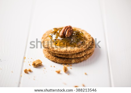 Oat cookies with kiwi jam and pecan nuts on white background. - stock photo