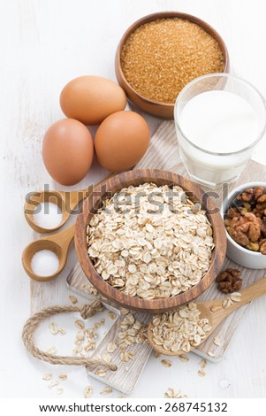 oat flakes and ingredients on a white wooden table, vertical, top view, close-up - stock photo