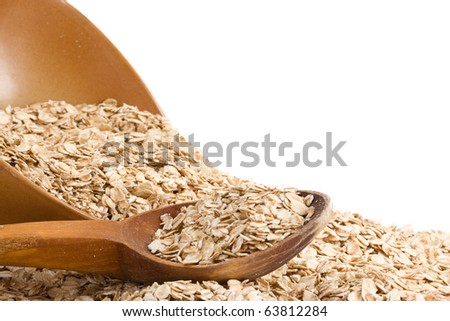 oat flakes and wood spoon in ceramic plate isolated on white background - stock photo