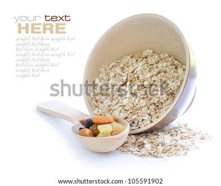 Oat flakes in bowl and wooden spoon with mix nuts and dry fruits on white background - stock photo