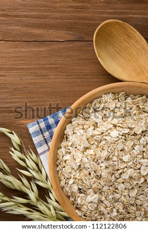 oat flakes in bowl on wooden background - stock photo