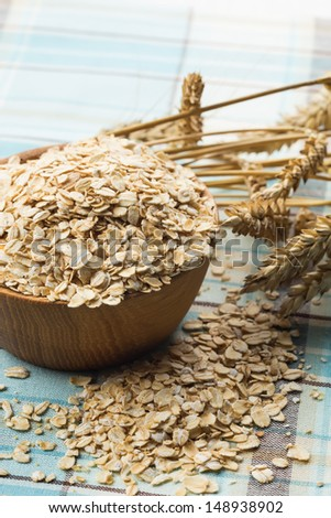 Oat flakes in wooden bowl. Selective focus. - stock photo