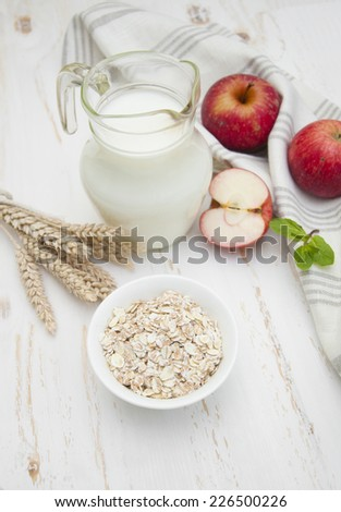 Oat flakes on a white bowl and jug of milk,apples and honey on a white wooden background  - stock photo